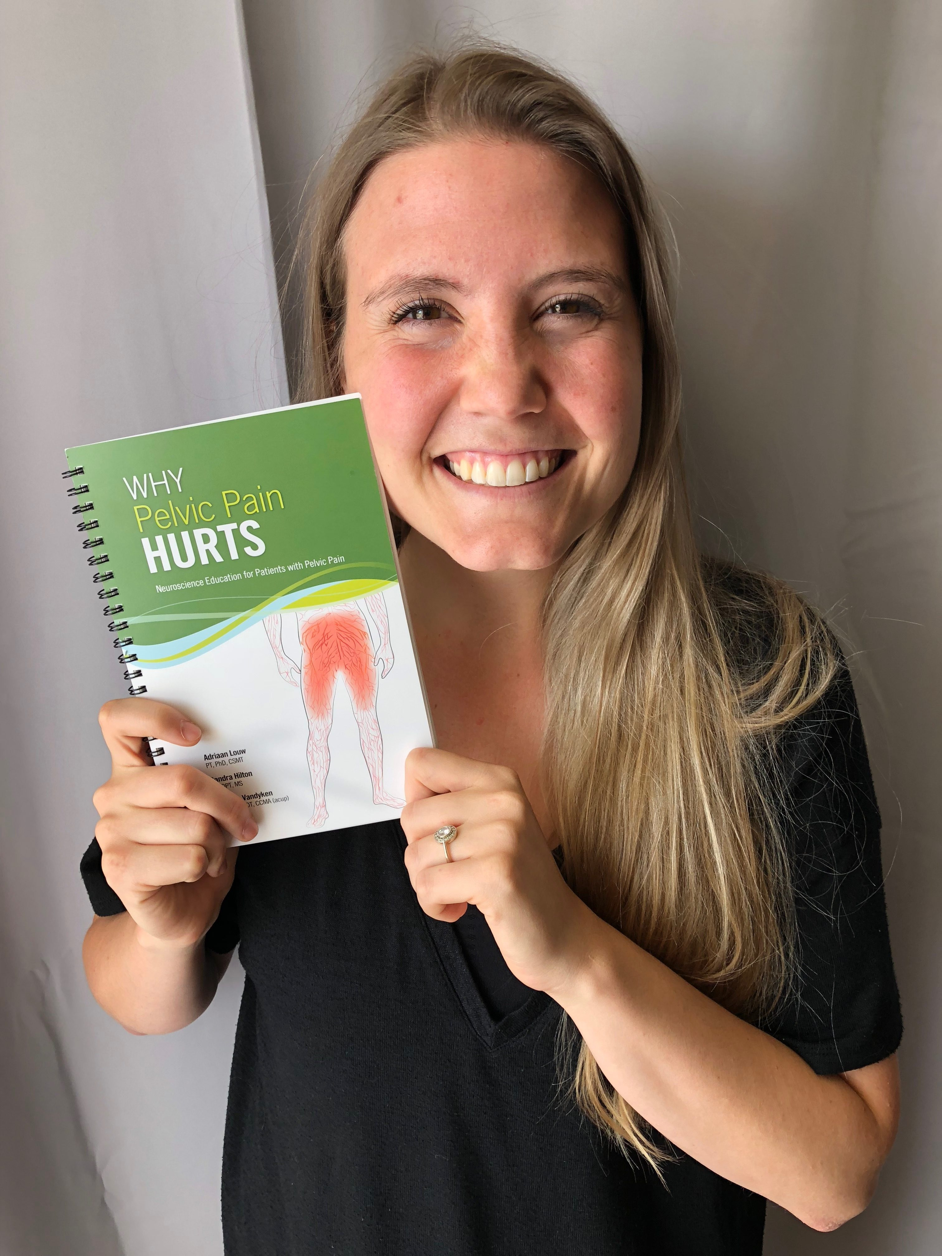 "A picture of Tori holding a copy of ""Why Pelvic Pain Hurts"""